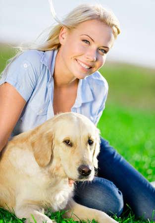 mujer con perro: Cerca de la mujer rubia con el perro perdiguero de oro en la hierba verde en el parque Foto de archivo