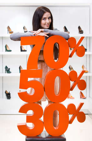Woman showing the percentage of sales on pumps in the shopping center against the window case with pumps photo