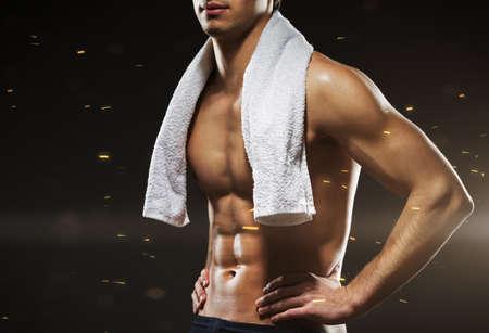 keep fit: Sportsmans torso, isolated on black sparkling background
