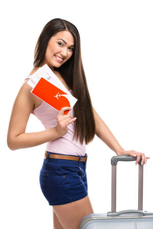 Half-length portrait of female tourist with travel suitcase and ticket, isolated on white photo