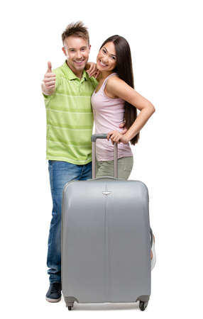 Full-length portrait of embracing couple with suitcase, isolated on white. Concept of romantic vacations and lovely honeymoon photo