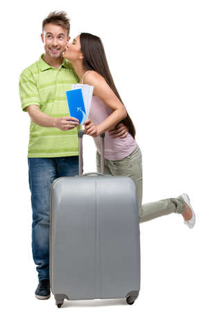 Full-length portrait of embracing couple with suitcase and tickets, isolated on white. Concept of romantic vacations and lovely honeymoon photo