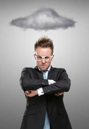 rage: Half-length portrait of business man in glasses with arms crossed standing under stormy cloud, isolated on grey Stock Photo