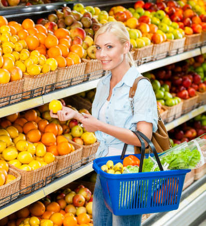 Girl at the shop choosing fruits and vegetables hands lemon and full of purchases hand cart photo