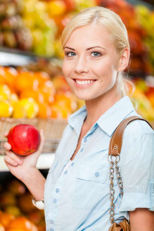 Girl at the market choosing fruits and vegetables hands fresh red apple photo