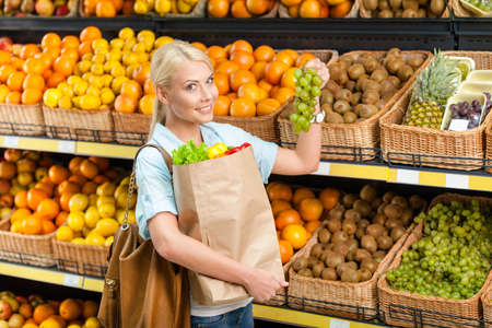 Choosing grape girl hands bag with fresh vegetables against the shelves of fruits in the shop photo