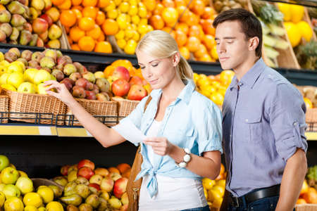 decides: Couple with shopping list against the stacks of fruits decides what to buy