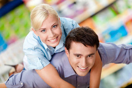 Woman embraces man in the shopping center. Concept of happy relationship and affection photo