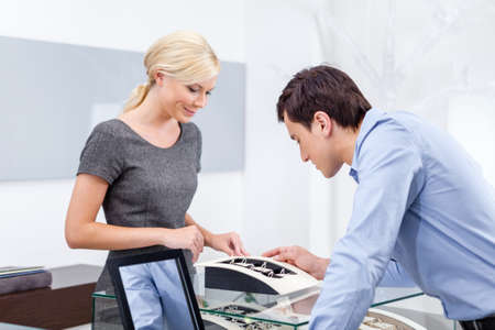 Male choosing engagement ring at jewelers shop. Concept of wealth and luxurious life photo