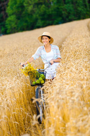 Woman rides cycle with apples and flowers in rye field. Concept of rural lifestyle and sport photo