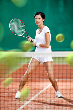 avocation: Sportswoman returning lots of balls at the tennis court. Concept of tournament preparation and healthy lifestyle