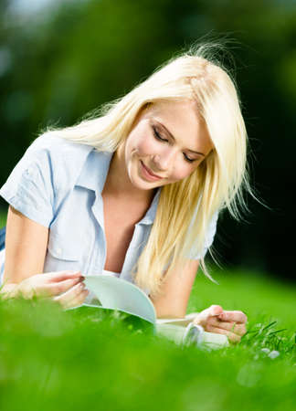 Female blonde student reads the book lying on the green grass in the park Stock Photo - 28624933