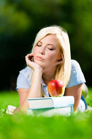 Pensive student girl lying on the green grass near red apple on the pile of books. Pleasant atmosphere of the studying process Stock Photo - 28624935