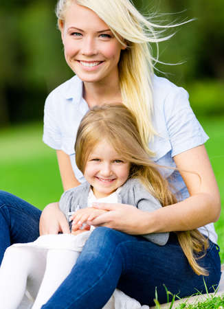 Mother and daughter sitting on the green grass embrace each other. Leisure time of happy family photo