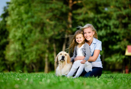 Mother with daughter and labrador sitting on the green grass at the summer park photo