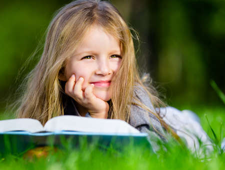 Pretty little girl reads interesting book lying on the green grass in the summer park photo