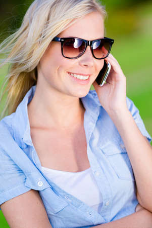 Pretty woman speaking on the cellphone in the summer park Stock Photo - 28624940
