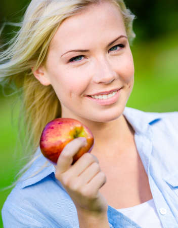 Close up of smiley blond girl holding red apple in her hand Stock Photo - 28624938