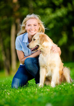 formats: Woman with labrador sitting on the green grass in the summer park