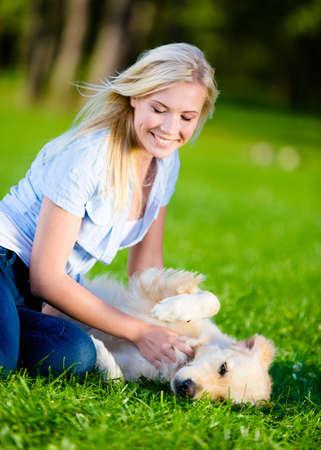 two stroke: Girl strokes golden retriever lying on the green grass in the park Stock Photo