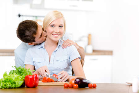 Man kisses lady while she is cooking sitting at the kitchen table full of vegetables photo