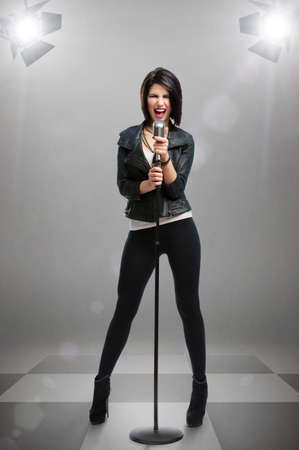 Full-length portrait of rock singer wearing leather jacket and keeping static mic under projectors, isolated on grey. Concept of rock music and rave photo