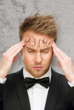 Portrait of business man with closed eyes putting hands on peeling off and cracked forehead, isolated on white. Concept of headache, high temperature and aging photo