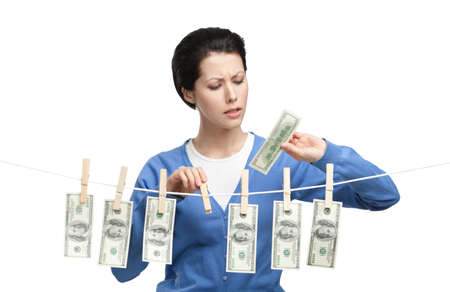 Woman hangs currency on the line with clothespins, isolated on white photo