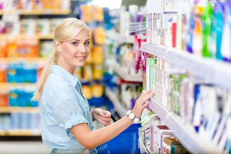 Side view of girl at the shop choosing cosmetics among the great variety of products. Concept of consumerism, retail and purchase Stock Photo