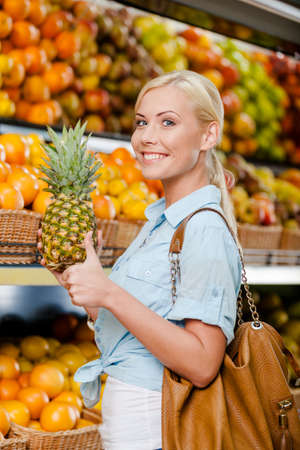 Girl at the shop choosing fruits and vegetables hands pineapple thumbs up photo