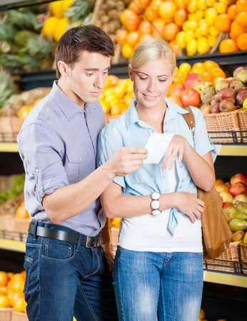 decides: Happy couple with shopping list against the stacks of fruits decides what to buy Stock Photo