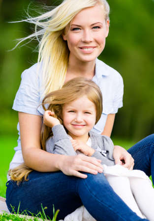 Mother and daughter sit on the grass embrace each other. Leisure time of happy family photo