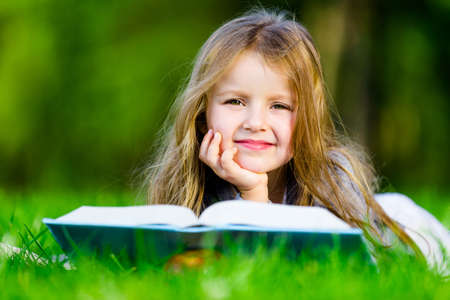 Girl reads interesting book lying on the green grass in the summer park photo