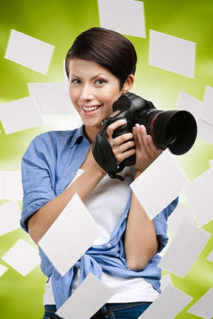 avocation: Woman takes images holding photographic camera on green white. Flying empty photos, copyspace