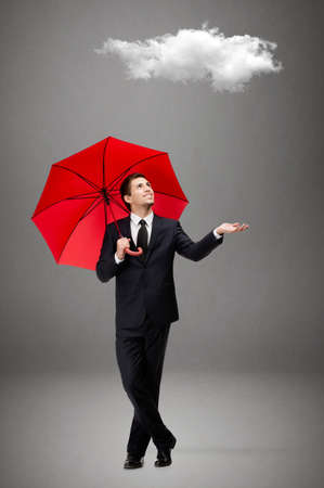 Palming up man with opened umbrella checks the rain and looks at the cloud overhead, isolated on grey photo