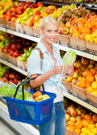 Girl at the shop choosing fruits and vegetables hands cabbage and full of purchases hand cart and thumbs up photo