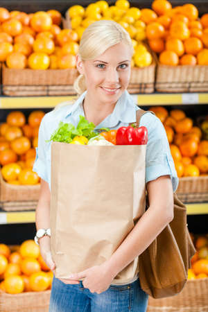 Girl hands bag with fresh vegetables against the shelves of fruits in the supermarket photo