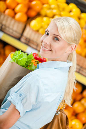 Girl hands paper bag with fresh vegetables against the shelves of fruits in the store photo
