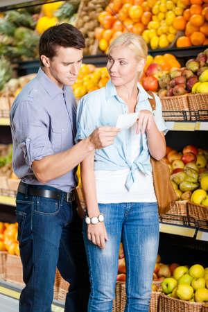 decide: Pareja joven con la lista de compras en contra de las pilas de frutas decide qu� comprar