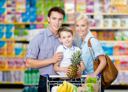 Half-length portrait of family in the shop. Son keeps pineapple over the shopping trolley full of food photo
