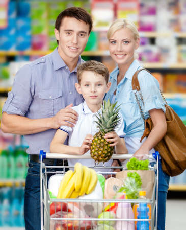 Half-length portrait of family in the market. Son keeps pineapple over the shopping trolley full of food photo