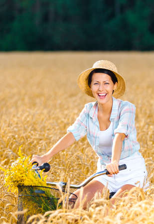 Girl pedals cycle with flowers in rye field. Concept of rural lifestyle and sport photo