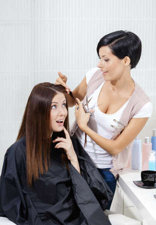 Hairdresser cuts hair of woman in hairdressing salon. Concept of fashion and beauty Stock Photo