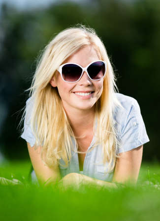 Young girl in sunglasses is lying on the grass photo