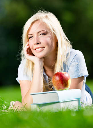 Dreaming girl lying on the grass near red apple on the pile of books. Pleasant atmosphere of the studying process photo