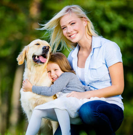 Mother and daughter with pet sitting on the green grass at the summer park photo