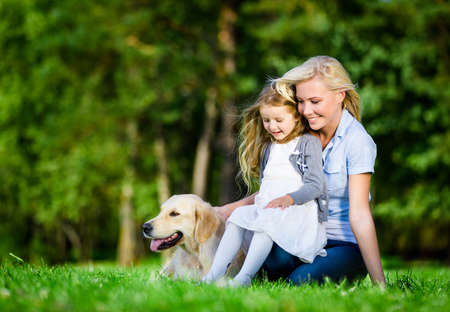 Mother and daughter with labrador sitting on the green grass at the summer park photo