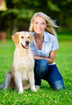 pretty blonde girl: Woman with golden retriever sitting on the green grass in the summer park