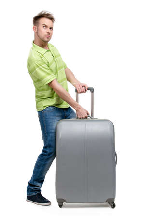 heave: Full-length portrait of man who lifts silver suitcase, isolated on white. Concept of travel and cool vacations Stock Photo