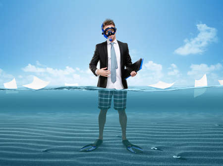 Full-length portrait of businessman wearing fins, snorkel and goggles hands folder with documents while standing in sea under blue sky